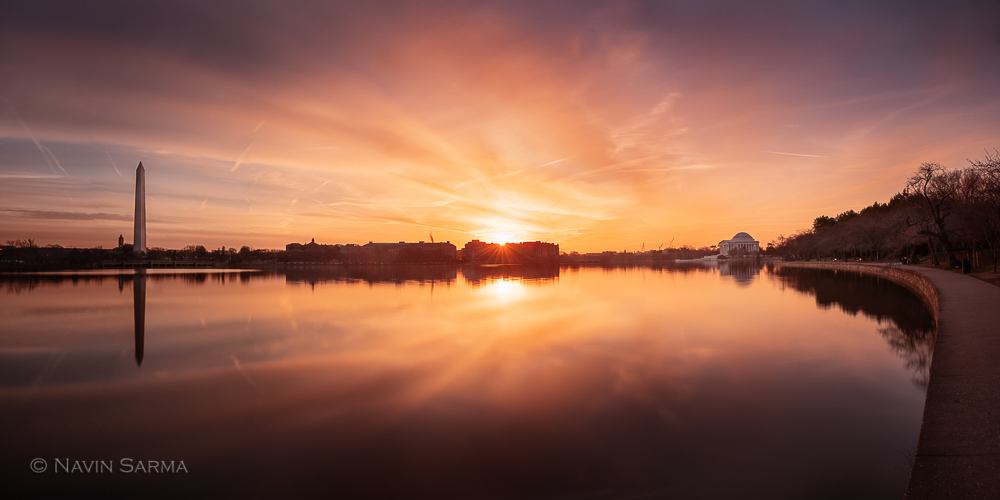 The Tidal Basin mirrors a dramatic sky at sunrise in Washington, D.C.