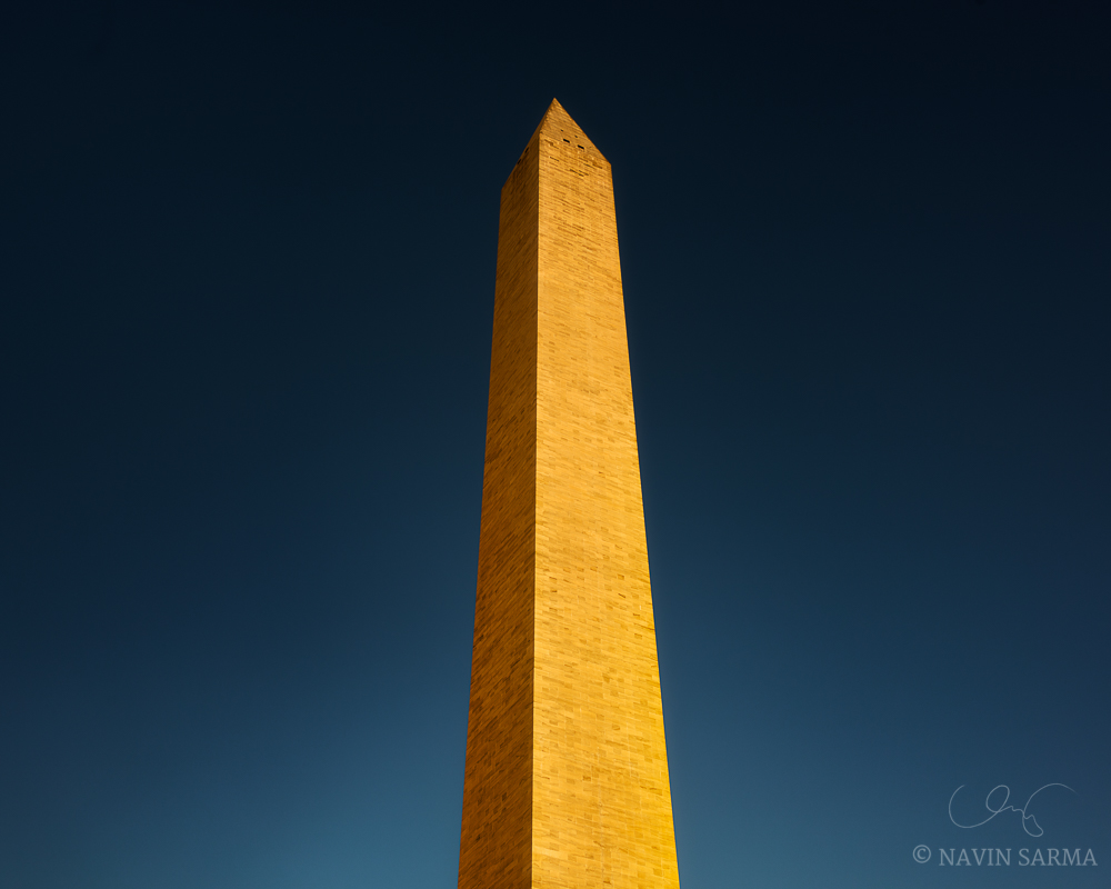 The Washington Monument basks in late evening sun under a darkening, clear blue sky