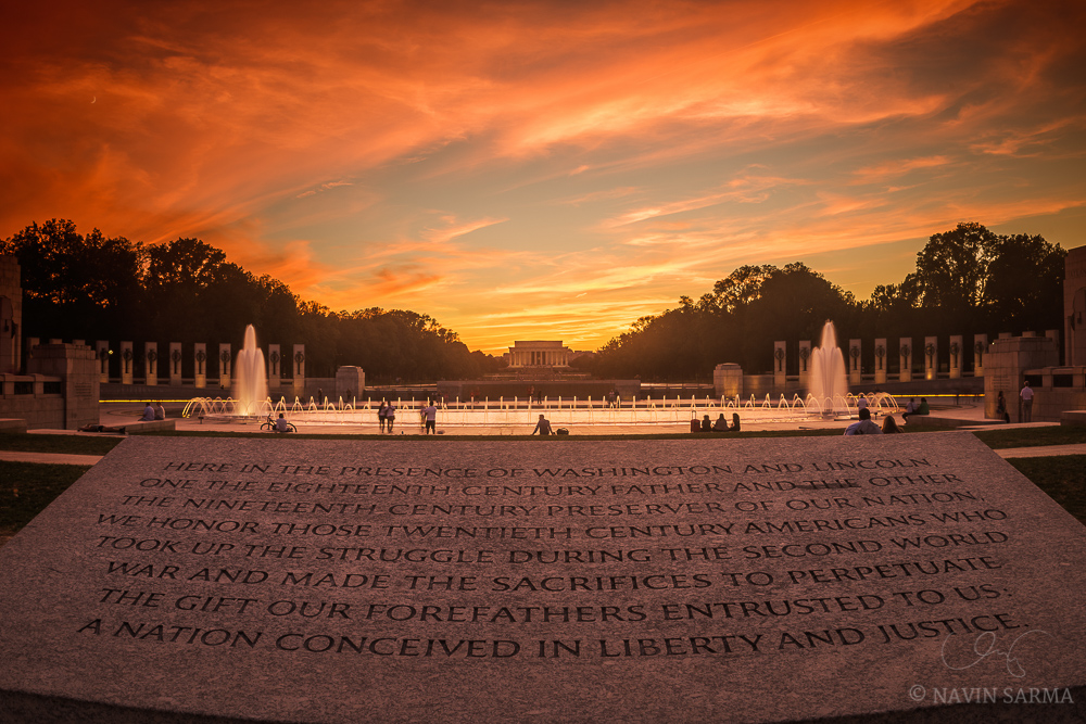 Vibrant oranges flush over the sky over the crescent moon at the World War II Memorial facing the Lincoln Memorial
