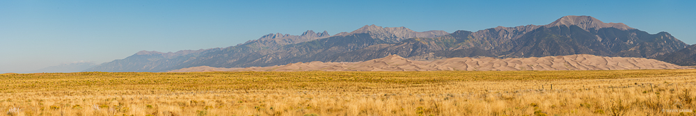 A wide view panorama of the Great Sand Dunes National Park below the Sangre de Cristo Mountains