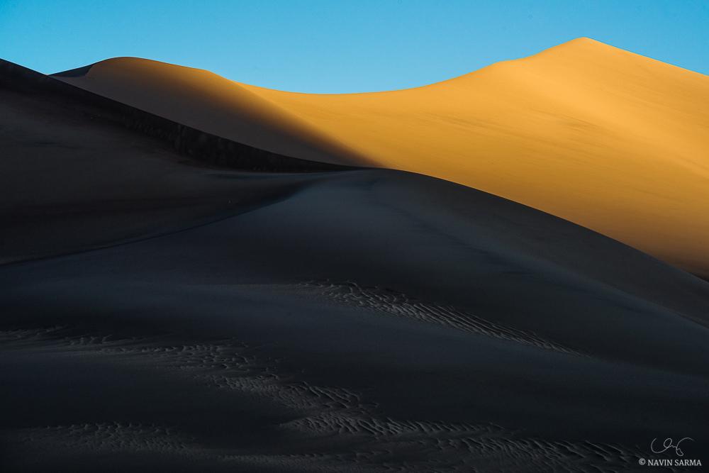 The first rays of sun contrast with the blue sky, shadows, and ridges of sculpted sand at Great Sand Dunes National Park