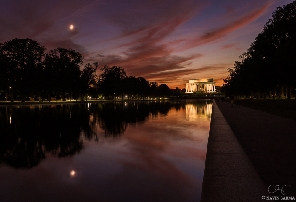 The crescent moon shines through pink and orange twilight clouds over the Lincoln Memorial