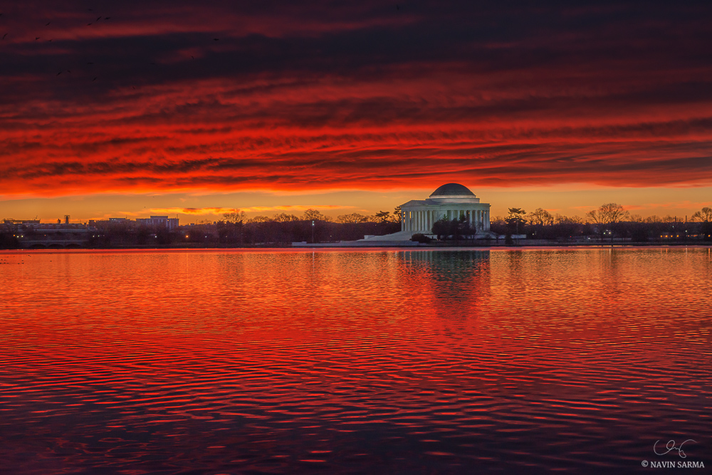 A vibrant red sunrise at the Jefferson Memorial