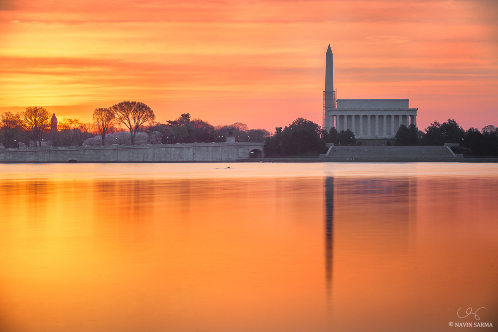 Orange and pink hues at sunrise looking towards the Lincoln Memorial, Memorial Bridge, the Washington Monument, and the Tidal Basin lined with cherry blossoms