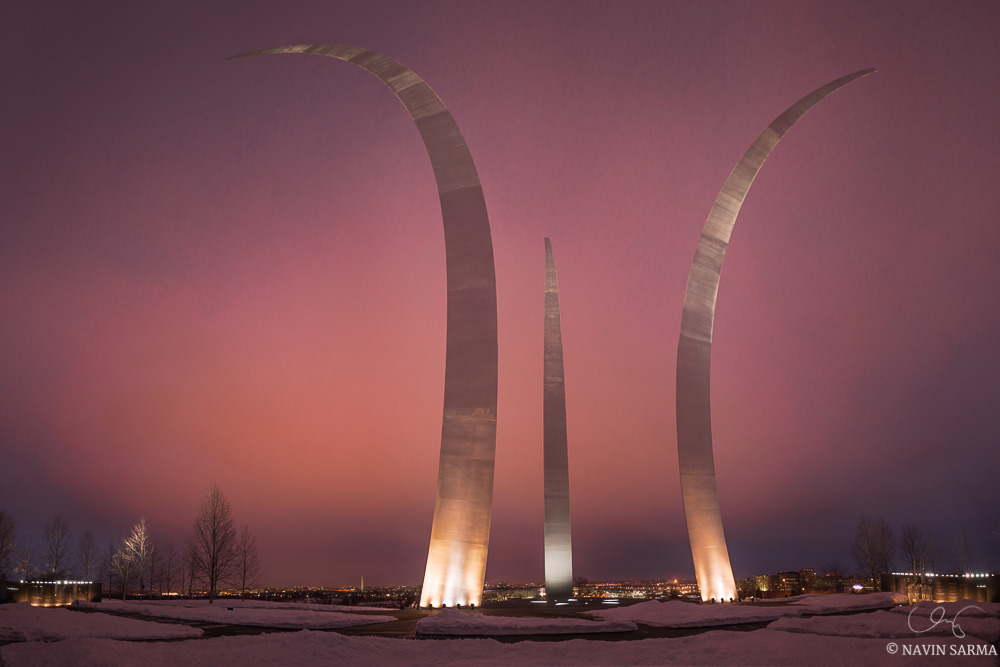 A reddish glow from city lights and the sunset as clouds pass by over the Air Force Memorial