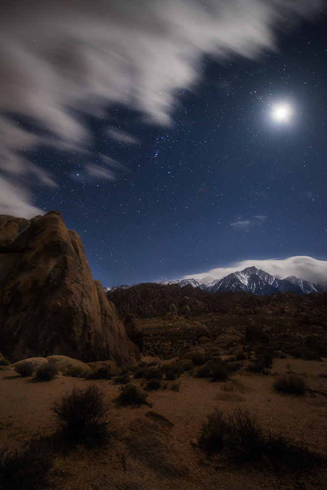The moon shines brightly through stars and just-forming clouds at Alabama Hills