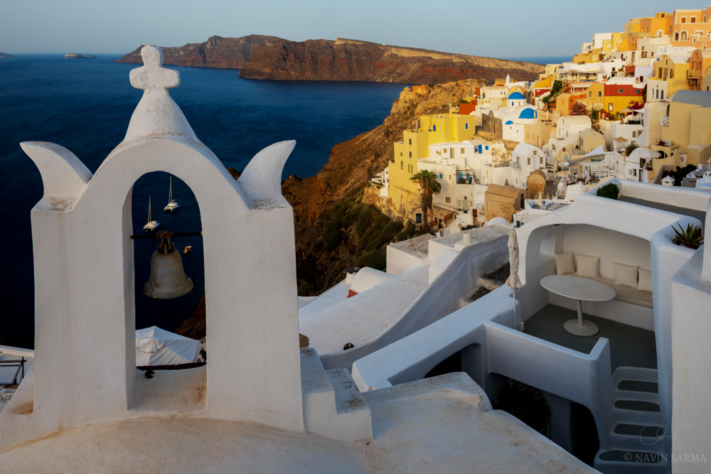 Rows of cavehouses bathed in early morning light as seen from a view also including church bells and docked boats