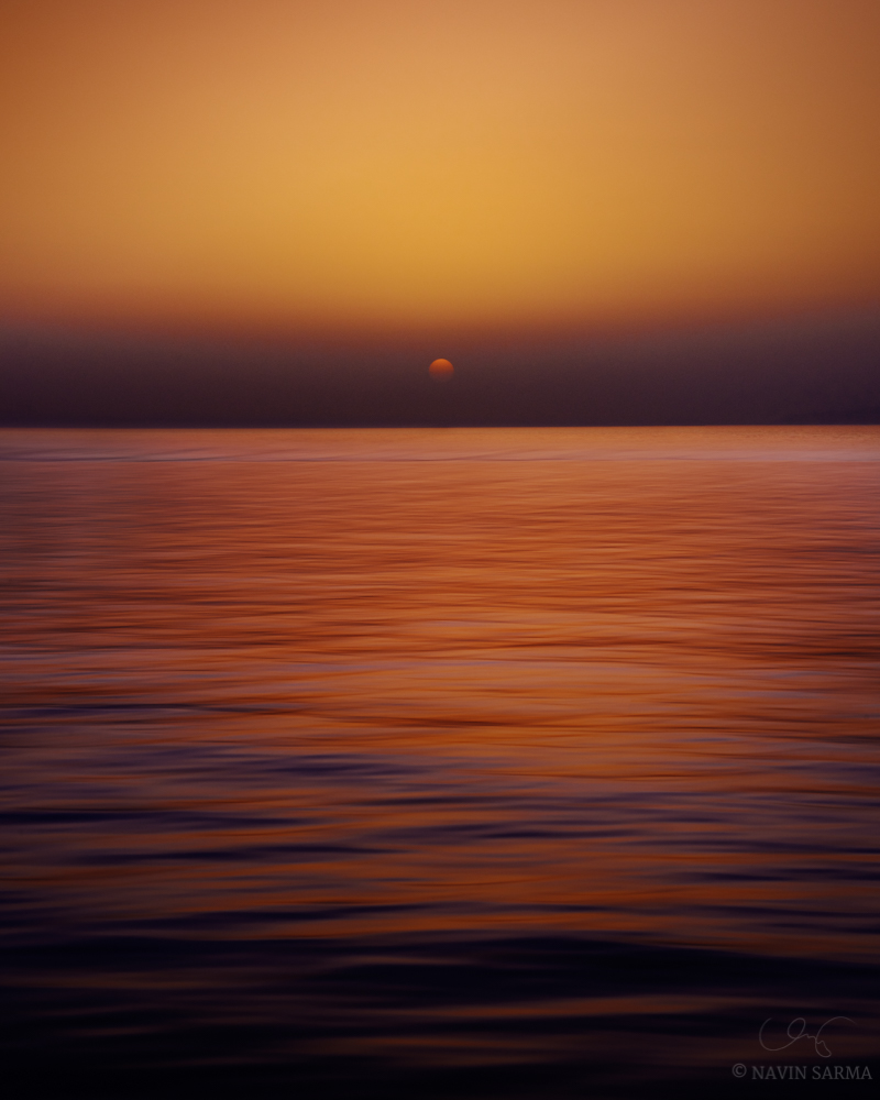 A classic Santorini sunset with a twist. This is a blended image of one exposure for the sun and another, pan motion shot to create a interesting texture in the water