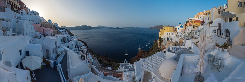A panoramic shows the layers of cave houses as they wrap around the ends of the island of Santorini at sunrise