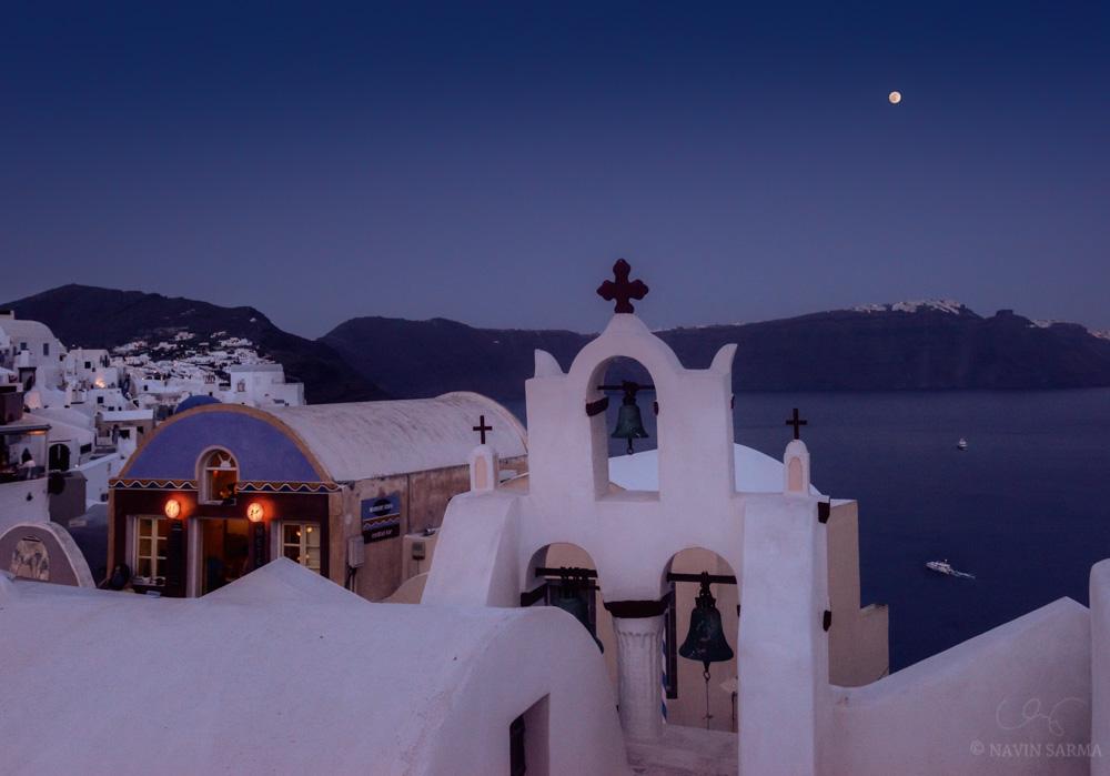 The moon rises over the twilight landscape of Oia, Santorini