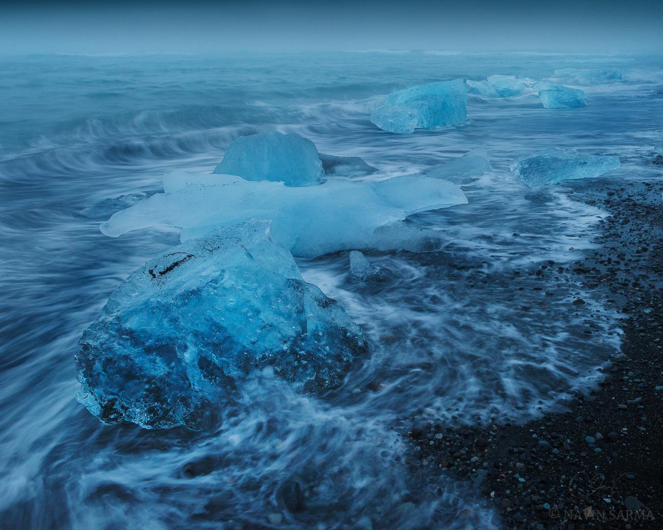 Icebergs line the shore of the black sand beach near Jökulsárlón