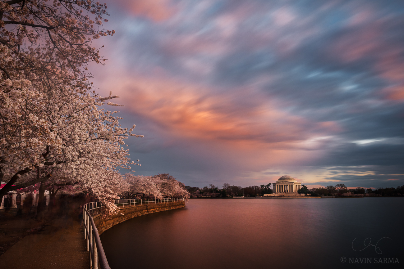 A long exposure streaks clouds during a colorful sunset at the Tidal Basin